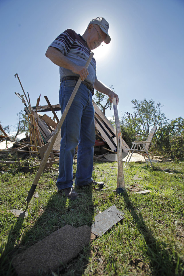 Photo - A.J. Pearcy finds an intact pick axe near the remains of one of his barns as residents cleanup following Tuesday's deadly tornado  on Wednesday, May 25, 2011, in Chickasha, Okla..  The axe was not where he left it but only had a broken handle.  Photo by Steve Sisney, The Oklahoman