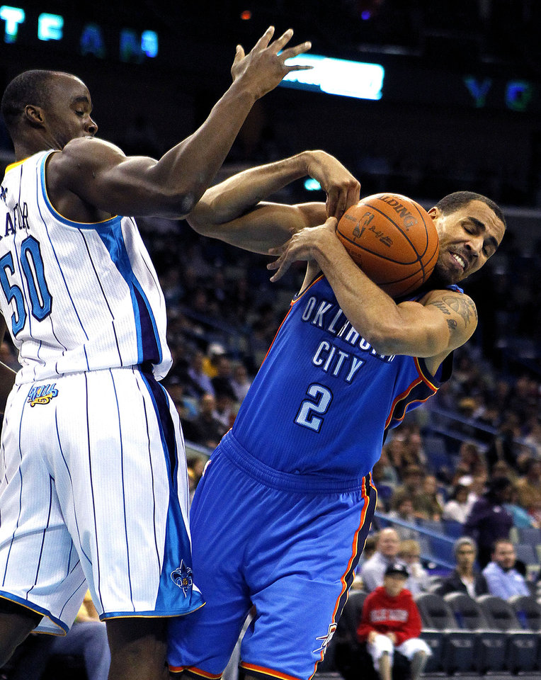 Photo - Oklahoma City Thunder's Thabo Sefolosha (2) loses control of the ball as he drives the lane against New Orleans Hornets' Emeka Okafor (50) in the first half of an NBA basketball game in New Orleans, Wednesday, Jan. 11, 2012. (AP Photo/Gerald Herbert)