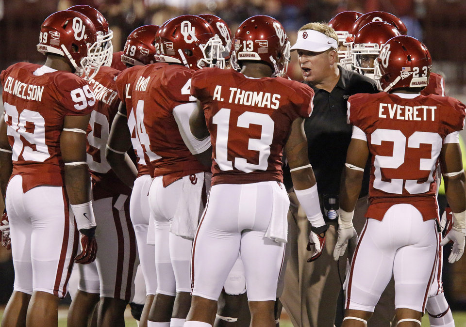 Photo - Oklahoma defensive coordinator Mike Stoops talks with players during a timeout in a college football game between the University of Oklahoma Sooners (OU) and the University of Louisiana Monroe Warhawks at Gaylord Family-Oklahoma Memorial Stadium in Norman, Okla., on Saturday, Aug. 31, 2013. Oklahoma won 34-0. Photo by Bryan Terry The Oklahoman