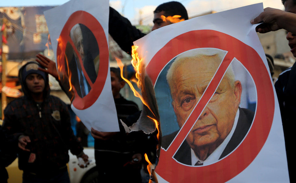 Photo - Palestinians burn a poster of the former Israel Prime Minister Ariel Sharon in Khan Younis, southern Gaza Strip, Saturday, Jan. 11, 2014. Sharon was loathed by many Palestinians as a bitter enemy who did his utmost to sabotage their independence hopes — by leading military offensives against them in Lebanon, the West Bank and Gaza and a settlement drive on the lands they want for a state. Sharon died Saturday, eight years after a debilitating stroke put him into a coma. He was 85. (AP Photo/Hatem Moussa)