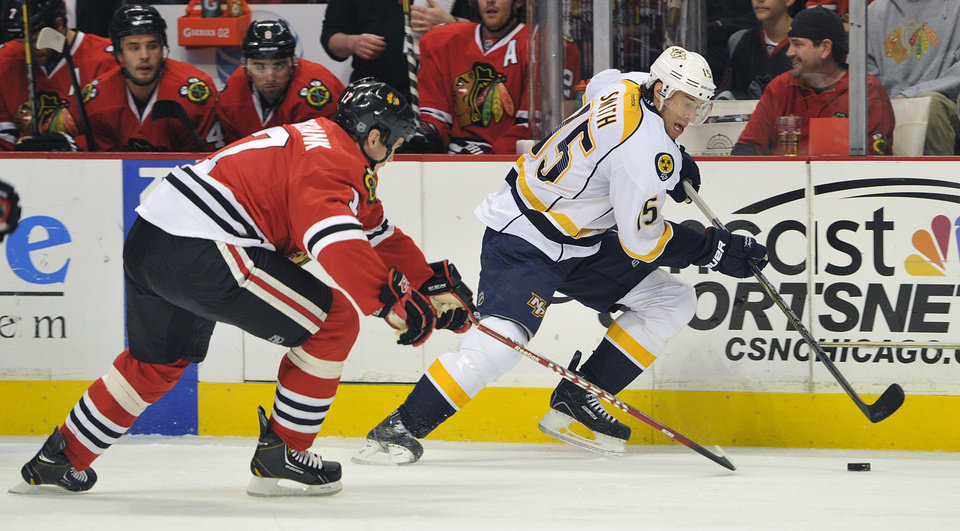Photo - Chicago Blackhawks' Brent Seabrook, left, and Nashville Predators' Craig Smith (15) fight for the puck during the first period of an NHL hockey game Friday, April 19, 2013, in Chicago. (AP Photo/Jim Prisching)