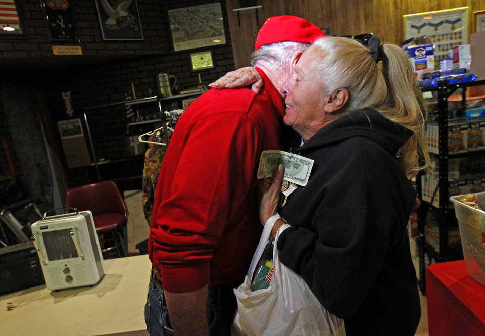 Photo - Carol Hefty hugs Secret Santa after he gave her a $100 dollar bill while she was looking for supplies at a temporary supply house at the Oakwood Heights VFW Post 9587 in the boro of Staten Island, New York, N.Y., Thursday, Nov. 29, 2012. The wealthy philanthropist from Kansas City, Mo. Secret Santa distributed $100 dollar bills to needy people at several locations in Elizabeth, N.J. and Staten Island. (AP Photo/Rich Schultz)
