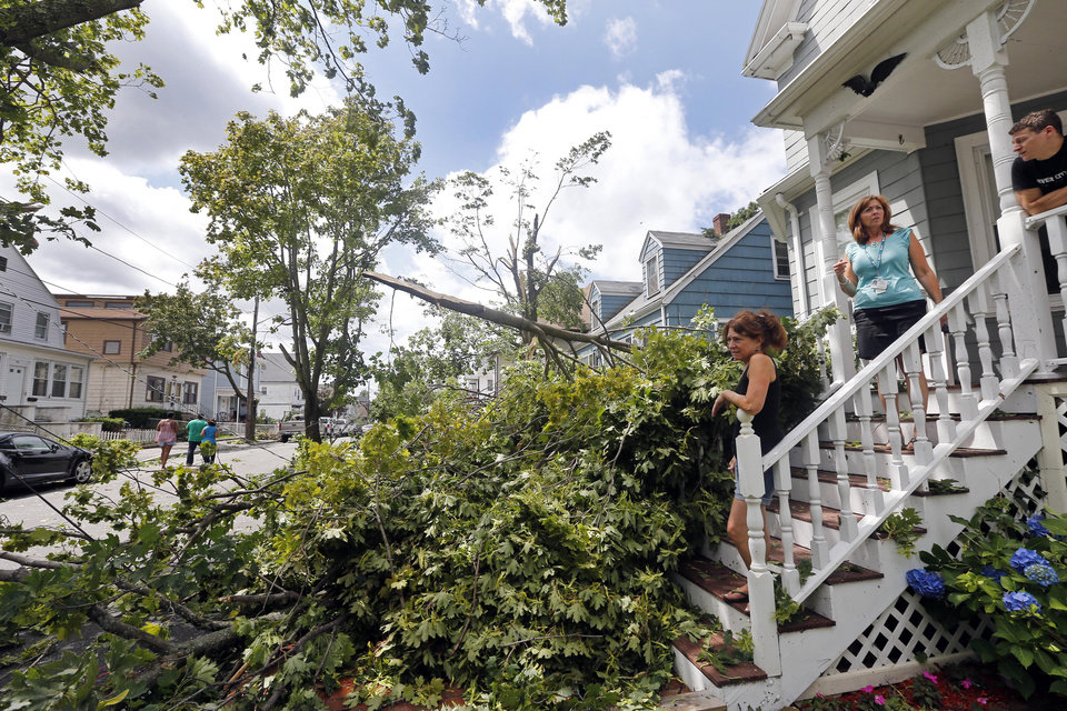 Photo - Ellen Bertino, left, and others look out at downed trees and power lines in Revere, Mass., Monday, July 28, 2014 after a tornado touched down. Revere Deputy Fire Chief Mike Viviano says the fire department in that coastal city has received dozens of calls reporting partial building and roof collapses, and downed trees and power lines. Viviano says there are no immediate reports of deaths or serious injuries. (AP Photo/Elise Amendola)
