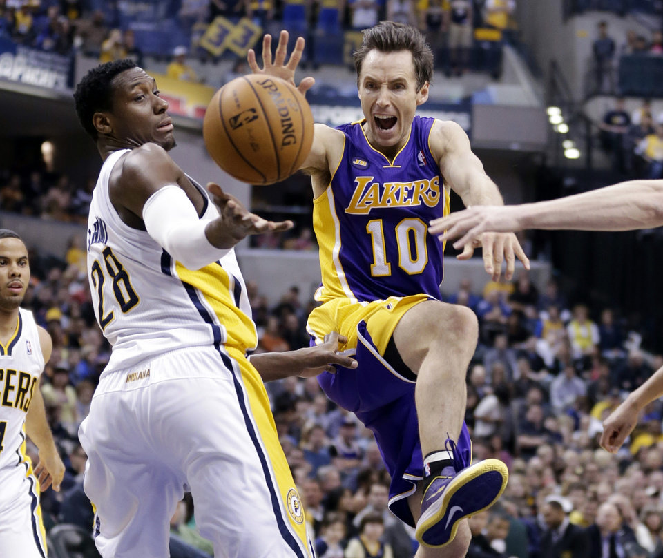 Photo - Los Angeles Lakers guard Steve Nash, right, loose the ball as he attempts a shot over Indiana Pacers center Ian Mahinmi in the first half of an NBA basketball game in Indianapolis, Friday, March 15, 2013.  (AP Photo/Michael Conroy)