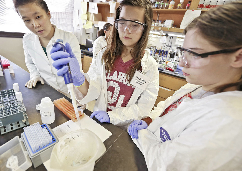 Photo - Scientist Jingrong Chen, left, works with students Jadelyn Holley and Callie Burdrick on a project during Putnam City Junior Scientist Days at Oklahoma Medical Research Foundation.  Photo by Chris Landsberger, The Oklahoman  CHRIS LANDSBERGER - CHRIS LANDSBERGER