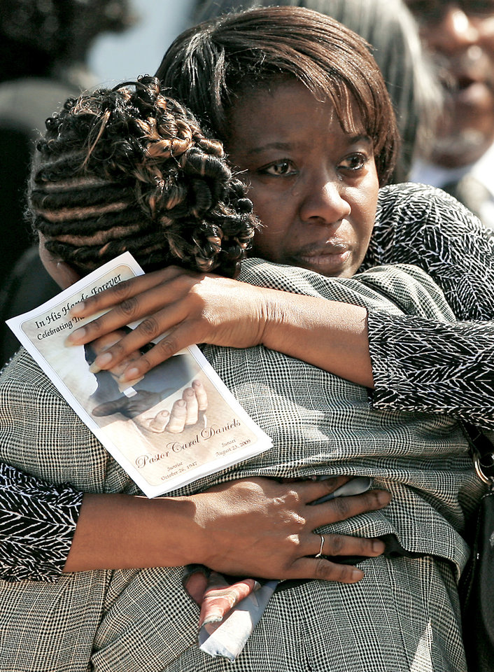 Left: Mourners  gather Monday  outside Greater New Zion Baptist Church in Oklahoma City after the funeral  of slain pastor the  Rev. Carol Daniels. The Oklahoma City woman was killed last week inside her church in Anadarko.  By John Clanton,  The Oklahoman