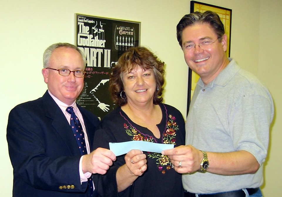 Photo - Bud Elder, left, and Rick Allen Lippert, judges for the Oklahoma Film Institute screenplay competition, present Linda McDonald with the $250 prize for the winning screenplay.