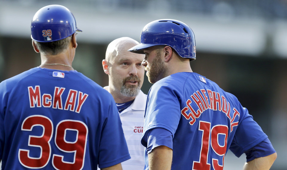 Photo - A Chicago Cubs trainer checks on Nate Schierholtz, right, after he was hit in the head by a throw while running to first base in the 13th inning of a baseball game against the San Diego Padres, Sunday, Aug. 25, 2013, in San Diego. The play came with the bases loaded and allowed a run to score. (AP Photo/Lenny Ignelzi)