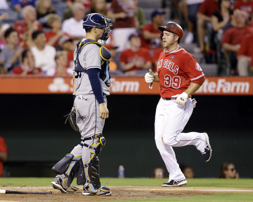 Photo - Los Angeles Angels' J.B. Schuck trots home past Tampa Bay Rays catcher Jose Lobaton, scoring on a Kole Calhoun base hit in the third inning of a baseball game in Anaheim, Calif., Monday, Sept. 2, 2013. (AP Photo/Reed Saxon)