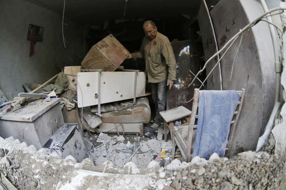 Photo - Valery who only gave his first name examines a room of his damaged house after shelling in the city of Slovyansk, Donetsk Region, eastern Ukraine Monday, June 30, 2014. Residential areas came under shelling on Monday morning from government forces. (AP Photo/Dmitry Lovetsky)