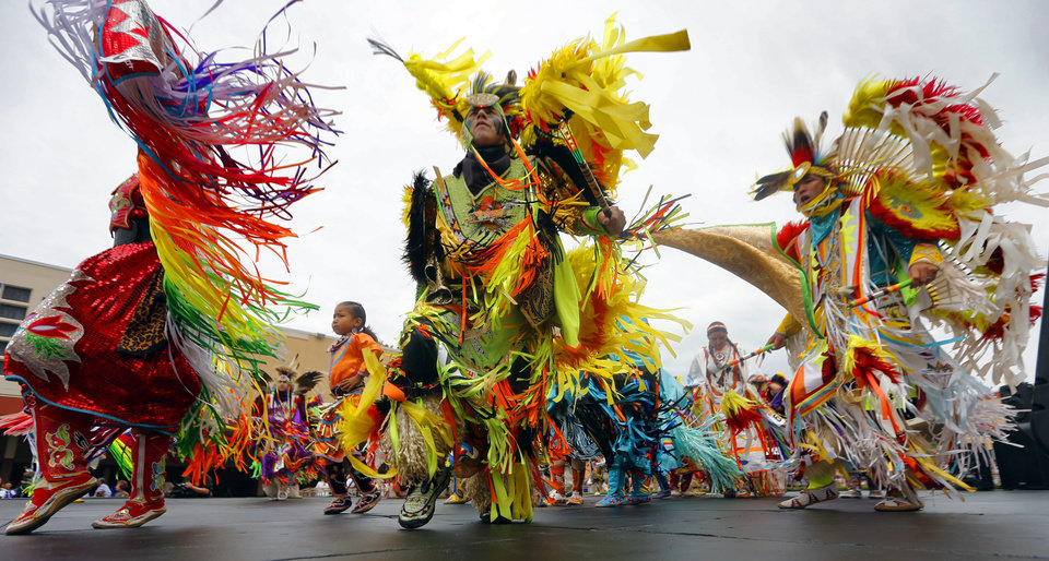 Photo - Dancers performs in the grand entry during the 2014 Red Earth Festival at Remington Park on Friday, June 6, 2014 in Oklahoma City, Okla. This is the first year for the festival to be held at Remington Park. Photo by Chris Landsberger, The Oklahoman
