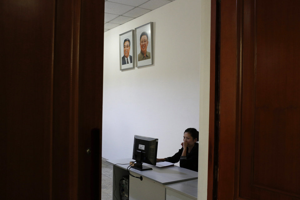 Photo - CAPTION CORRECTION, CORRECTS YEAR IN SECOND SENTENCE - FILE - In this Sept. 20, 2012 file photo, a North Korean woman sits in a computer room near portraits of the country's late leaders, Kim Il Sung and Kim Jong Il, at the Kim Chaek University of Technology in Pyongyang, North Korea. Google's executive chairman Eric Schmidt is preparing to travel to one of the last frontiers of cyberspace: North Korea. Schmidt will be traveling to North Korea on a private trip led by former New Mexico Gov. Bill Richardson that could take place as early as this month, sources told The Associated Press on Wednesday, Jan. 2, 2013. The sources, two people familiar with the group's plans, asked not to be named because the visit had not been made public. (AP Photo/Vincent Yu, File)