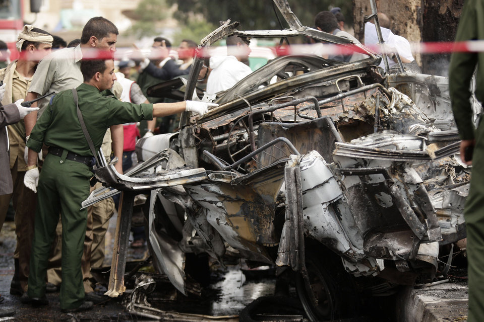 Photo -   Forensic policemen collect evidence at the site of a car bomb attack targeting the motorcade of the country's defense minister in Sanaa, Yemen, Tuesday, Sept. 11, 2012. Yemeni officials say a car bomb targeting the motorcade of the country's defense minister has killed several people, but the minister escaped unharmed. (AP Photo/Hani Mohammed)