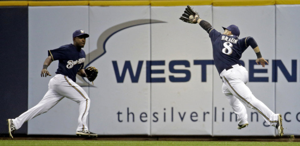 Photo - Milwaukee Brewers' Elian Herrera watches as teammate Ryan Braun (8) makes a running catch on a ball hit by Pittsburgh Pirates' Jordy Mercer during the seventh inning of a baseball game Wednesday, May 14, 2014, in Milwaukee. (AP Photo/Morry Gash)