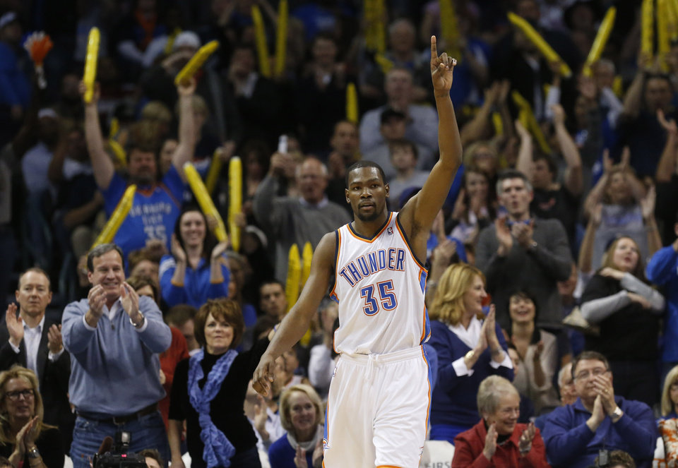 Photo - Oklahoma City Thunder forward Kevin Durant (35) and the crowd react to a dunk by Durant against the San Antonio Spurs in the fourth quarter of an NBA basketball game in Oklahoma City, Monday, Dec. 17, 2012. Oklahoma City won 107-93. (AP Photo/Sue Ogrocki)