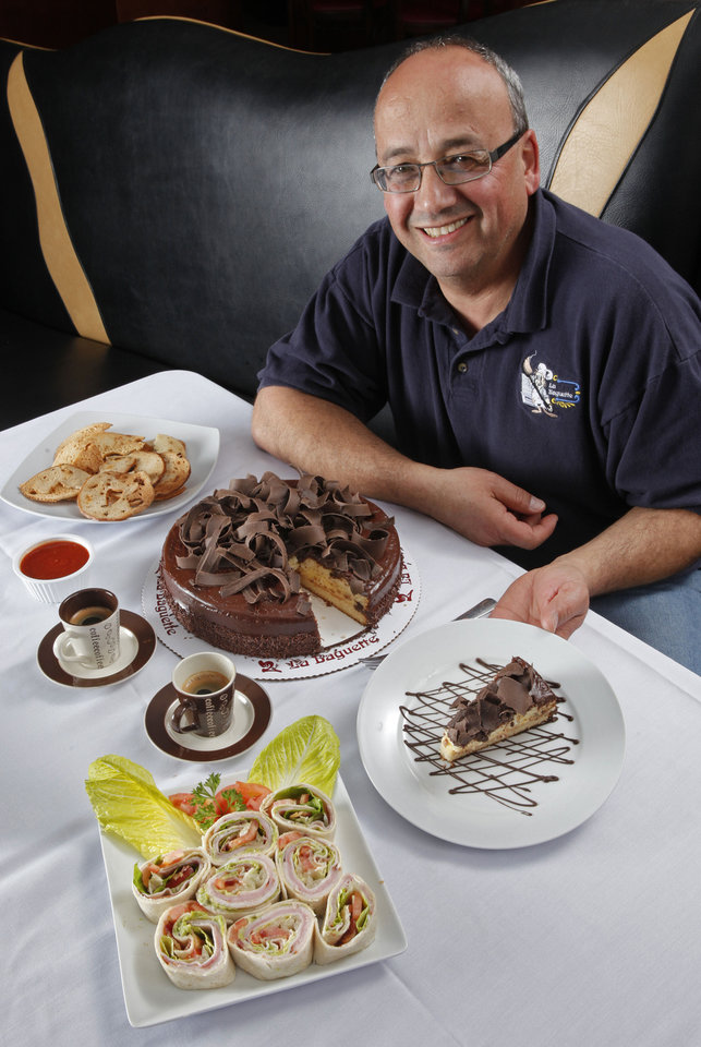 Photo - Rudy Khouri, pastry chef at La Baguette, shows a slice of Boston Cream Pie in Norman  STEVE SISNEY - THE OKLAHOMAN