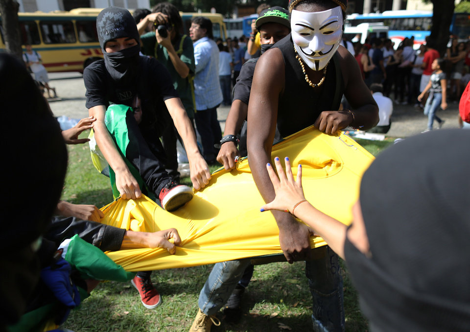 Photo - Masked anti-World Cup protesters rip apart a Brazilian national team soccer jersey during a demonstration, in downtown Rio de Janeiro, Brazil, Thursday, June 12, 2014, hours before the first World Cup match was to be played in Sao Paulo. (AP Photo/Leo Correa)