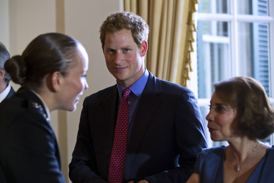 Photo - Britain's Prince Harry along with wife of the British Ambassador to the U.S. Lady Westmacott, right, greet attendees before a reception in the Prince's honor at the Ambassador's residence in Washington, Thursday, May 9, 2013. (AP Photo/Jim Lo Scalzo, Pool)
