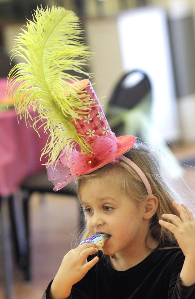 Photo - Hannah Snyder, 5, eats at the Daddy-Daughter Mad Hatter Tea Party at the Edmond Multi-purpose Community Center Sunday, Feb. 12, 2012. Hannah's twin sister Olivia was also at the party. Photo by Doug Hoke, The Oklahoman ORG XMIT: OKC1202091803570754