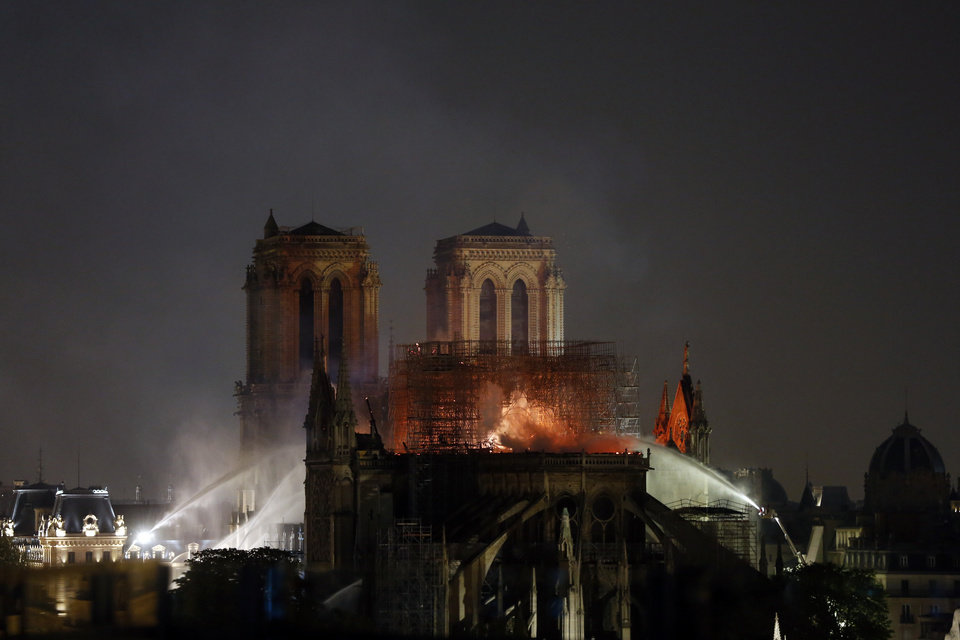 Photo - Firefighters tackle the blaze as flames and smoke rise from Notre Dame cathedral as it burns in Paris, Monday, April 15, 2019. Massive plumes of yellow brown smoke is filling the air above Notre Dame Cathedral and ash is falling on tourists and others around the island that marks the center of Paris. (AP Photo/Thibault Camus)