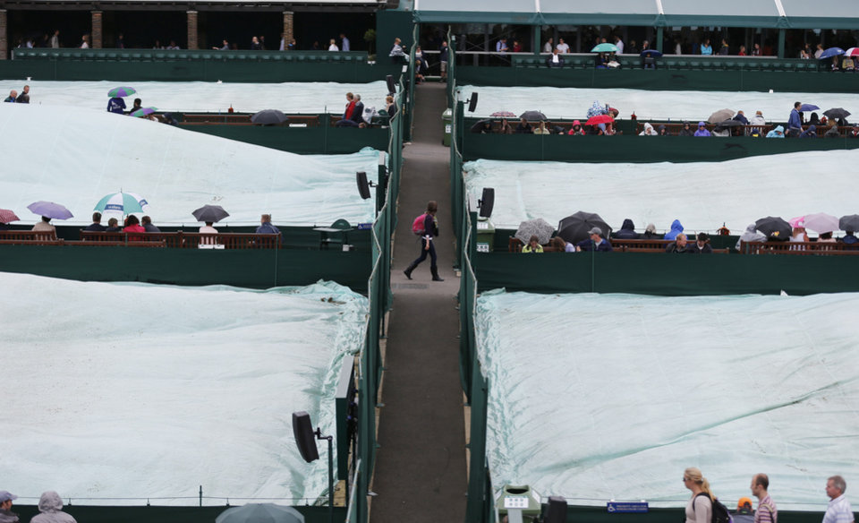 Photo - Courts are covered as rain delays the start of matches at the All England Lawn Tennis Championships in Wimbledon, London, Friday, June 27, 2014. (AP Photo/Ben Curtis)