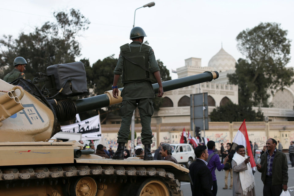 Photo - An Egyptian protester takes a picture with his mobile of another in front of an Egyptian army tank outside the presidential palace, background, in Cairo, Egypt, Saturday, Dec. 8, 2012. Egypt's military warned Saturday of 'disastrous consequences' if the crisis that sent tens of thousands of protesters back into the streets is not resolved, signaling the army's return to an increasingly polarized and violent political scene.(AP Photo/Hassan Ammar)