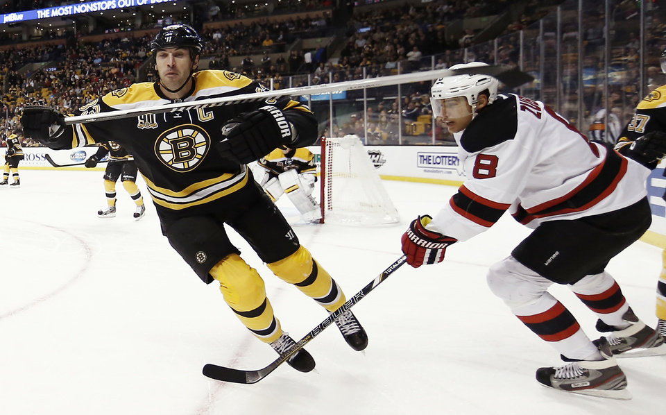 Photo - Boston Bruins' Zdeno Chara, left, of Slovakia, is tripped by New Jersey Devils' Dainius Zubrus, of Lithuania, during the first period of an NHL hockey game in Boston, Saturday, Oct. 26, 2013. (AP Photo/Winslow Townson)