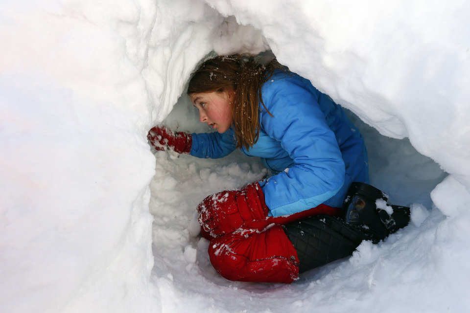 Claire Stout, 12, burrows into a pile of plowed snow near her home in Maplewood, N.J. on Saturday, Feb. 9, 2013. The Northeast storm dumped over a foot of snow in northern N.J. (AP Photo/Rich Schultz) ORG XMIT: NJRS101