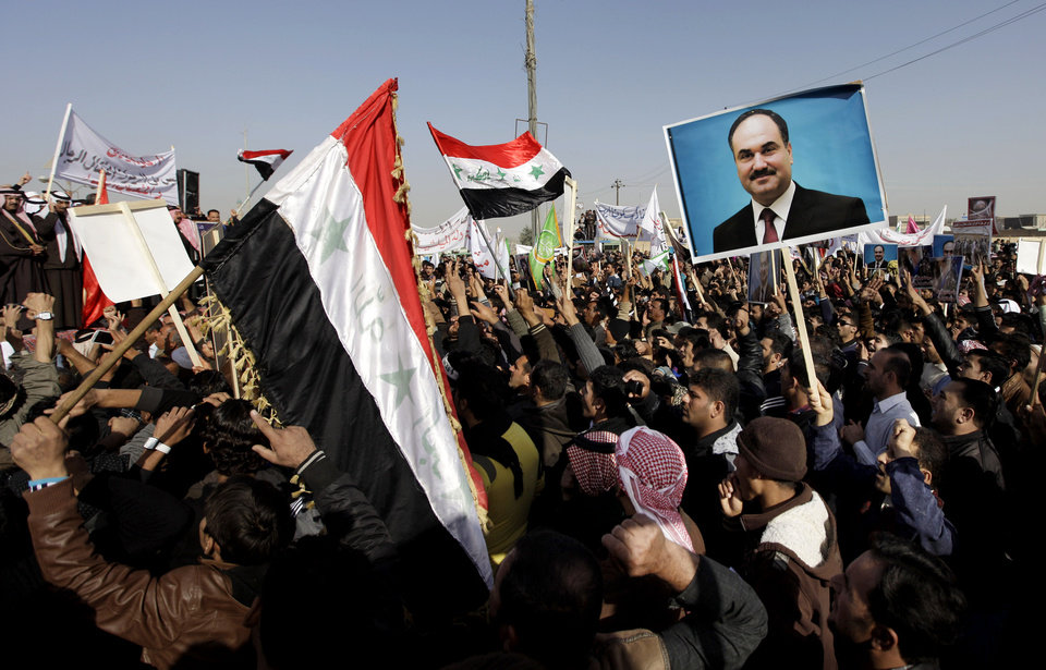 Photo - Protesters chant slogans against the Iraq's Shiite-led government as they wave national flags and hold posters of the Sunni Finance Minister Rafia al-Issawi during a demonstration in Fallujah, 40 miles (65 kilometers) west of Baghdad, Iraq, Sunday, Dec. 23, 2012. Thousands of protesters have demonstrated in Iraq's western Sunni heartland following the arrest of bodyguards assigned to the finance minister, who draws support from the area. (AP Photo/ Khalid Mohammed)