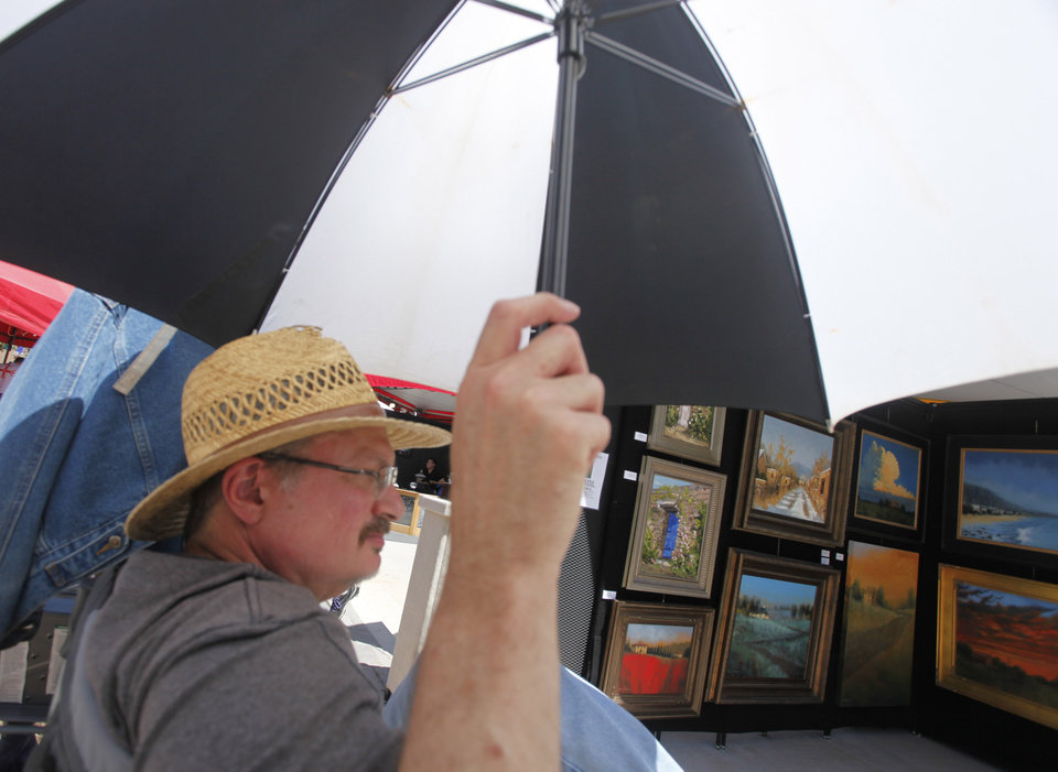 Artist Thomas Stotts keeps out of the sun during opening day of the Festival of the Arts in downtown Oklahoma City TUesday, April 24, 2012. Photo by Doug Hoke, The Oklahoman