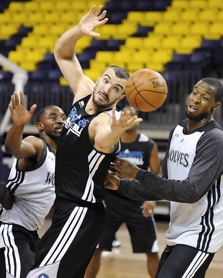Minnesota Timberwolves center Nikola Pekovic, center, reaches for the ball during their first day of NBA basketball training camp, Tuesday, Oct. 2, 2012, at Minnesota State University in Mankato, Minn. (AP Photo/The Mankato Free Press, Pat Christman)