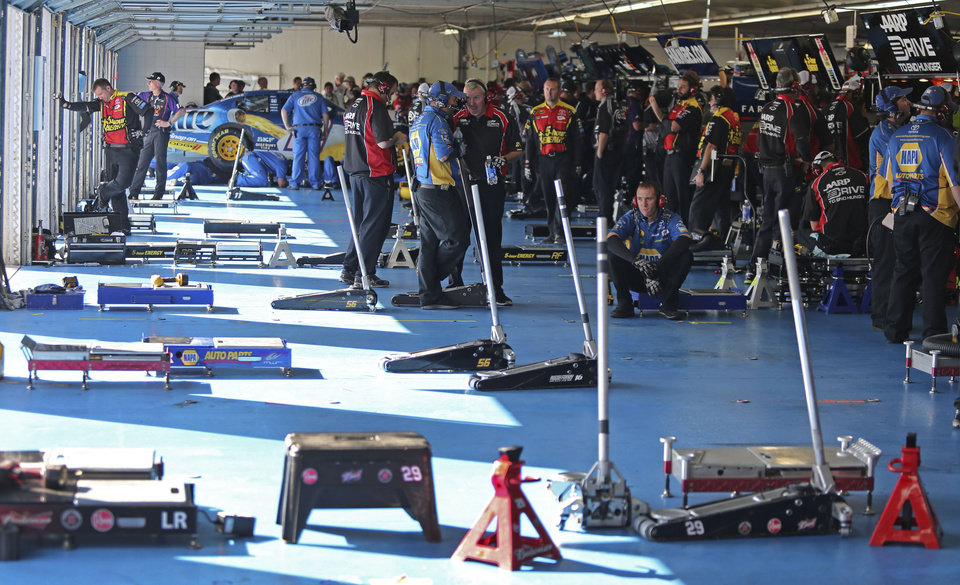 Photo -   Crew members wait in an empty garage during practice for Saturday's NASCAR Bank of America 500 Sprint Cup series auto race in Concord, N.C., Friday, Oct. 12, 2012. (AP Photo/Bob Jordan)