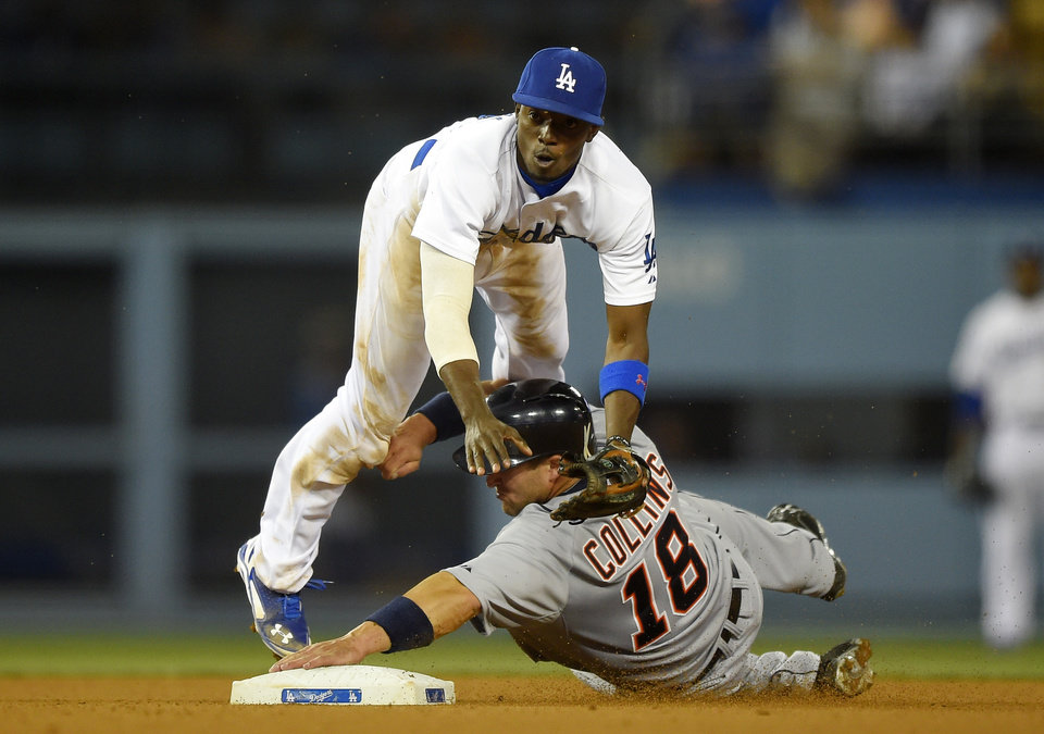 Photo - Detroit Tigers' Tyler Collins, below, is forced out at second as Los Angeles Dodgers second baseman Dee Gordon throws out Alex Gonzalez at first during the eighth inning of a baseball game, Wednesday, April 9, 2014, in Los Angeles. (AP Photo/Mark J. Terrill)