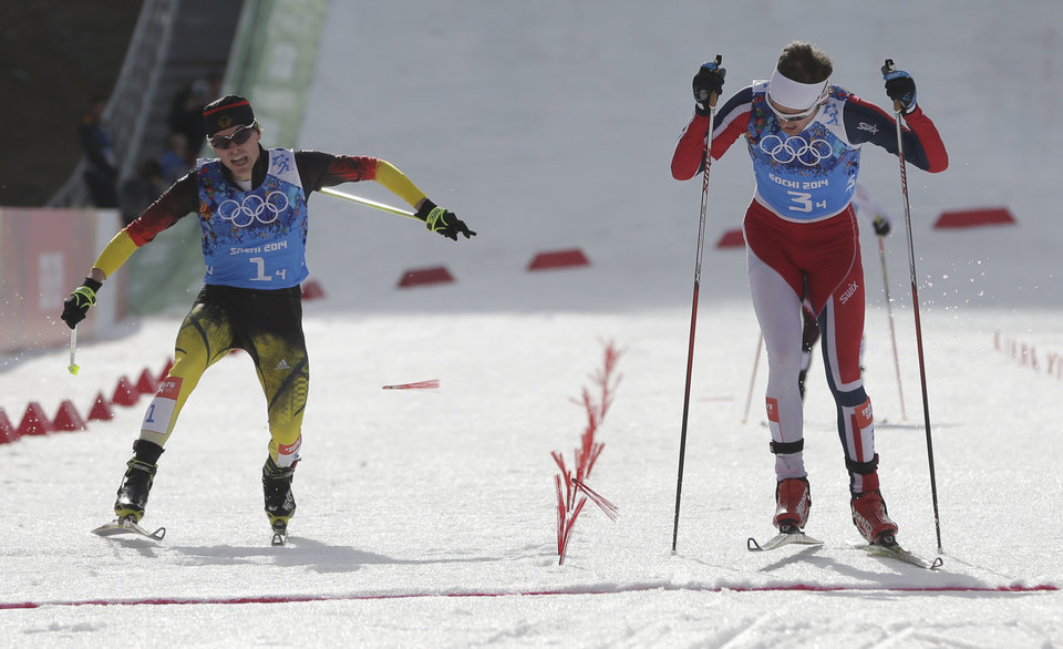 Photo - Norway's Joergen Graabak, right, crosses the finish line to win gold ahead of silver medal winner Germany's Fabian Riessle, left, during the cross-country portion of the Nordic combined Gundersen large hill team competition at the 2014 Winter Olympics, Thursday, Feb. 20, 2014, in Krasnaya Polyana, Russia. (AP Photo/Matthias Schrader)