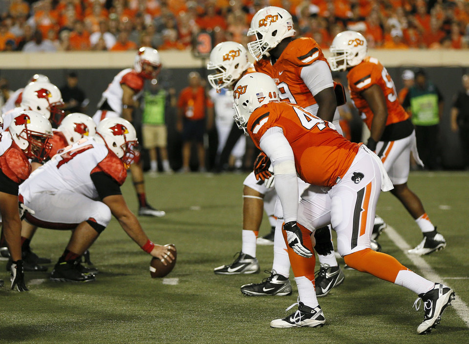Photo - OSU defenders stand on third down during a college football game between the Oklahoma State University Cowboys (OSU) and the Lamar University Cardinals at Boone Pickens Stadium in Stillwater, Okla., Saturday, Sept. 14, 2013. Photo by Nate Billings, The Oklahoman  NATE BILLINGS