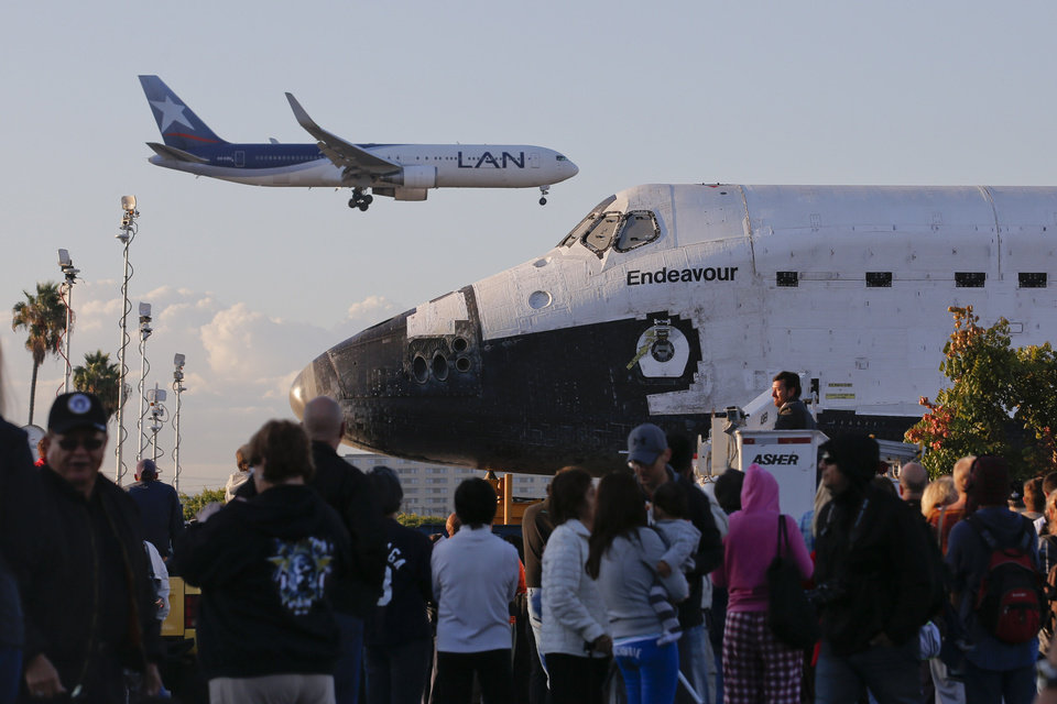 Spectators gather to watch the space shuttle Endeavour near Los Angeles Internal Airport in Los Angeles, Friday, Oct. 12, 2012. Endeavour's 12-mile road trip kicked off shortly before midnight Thursday as it moved from its Los Angeles International Airport hangar en route to the California Science Center, its ultimate destination, said Benjamin Scheier of the center. (AP Photo/Jae C. Hong)