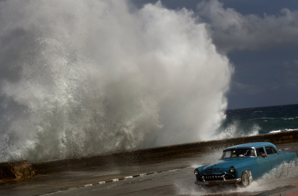 Photo -   A driver maneuvers his classic American car along a wet road as a wave crashes against the Malecon in Havana, Cuba, Thursday, Oct. 25, 2012. Hurricane Sandy blasted across eastern Cuba on Thursday as a potent Category 2 storm and headed for the Bahamas after causing at least two deaths in the Caribbean. (AP Photo/Ramon Espinosa)