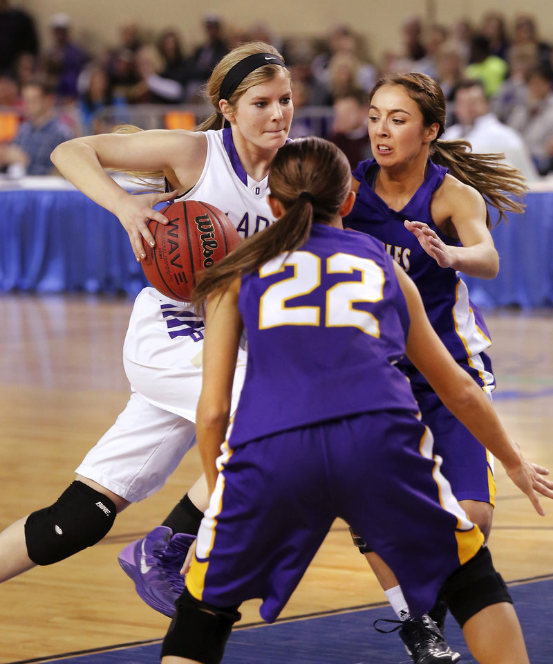 Photo - Okarche's Kenadey Grellner drives between two Red Oak defenders on her way to a lay-up  in the  Class B girls high school basketball championship game with a brace on her right leg.  Okarche defeated Red Oak, 66-41, in the Jim Norick Arena at State Fair Park on  Saturday, March 8, 2014.   Photo by Jim Beckel, The Oklahoman