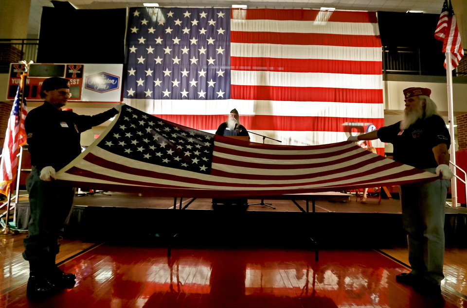 Oklahoma Veterans School Flag Program members demonstrate the 13 folds of the American flag during Yukon High School's Veterans Day celebration Monday. Photos by Chris Landsberger, The Oklahoman