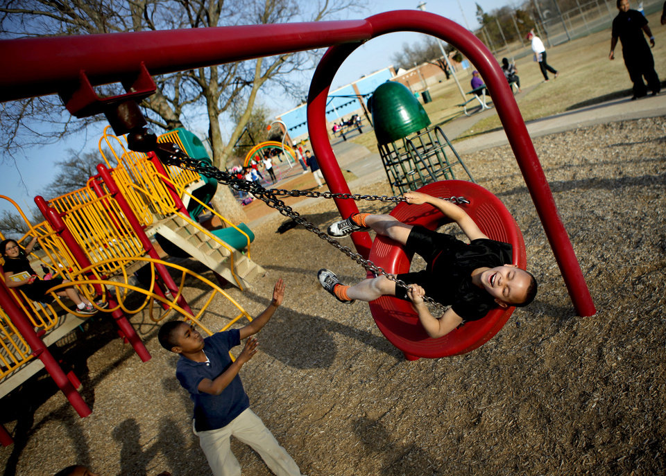 Randy Green, 6, laughs as Navy Hill, 8, pushes him in a tire swing at the Boys and Girls Club. Photo by Bryan Terry, The Oklahoman