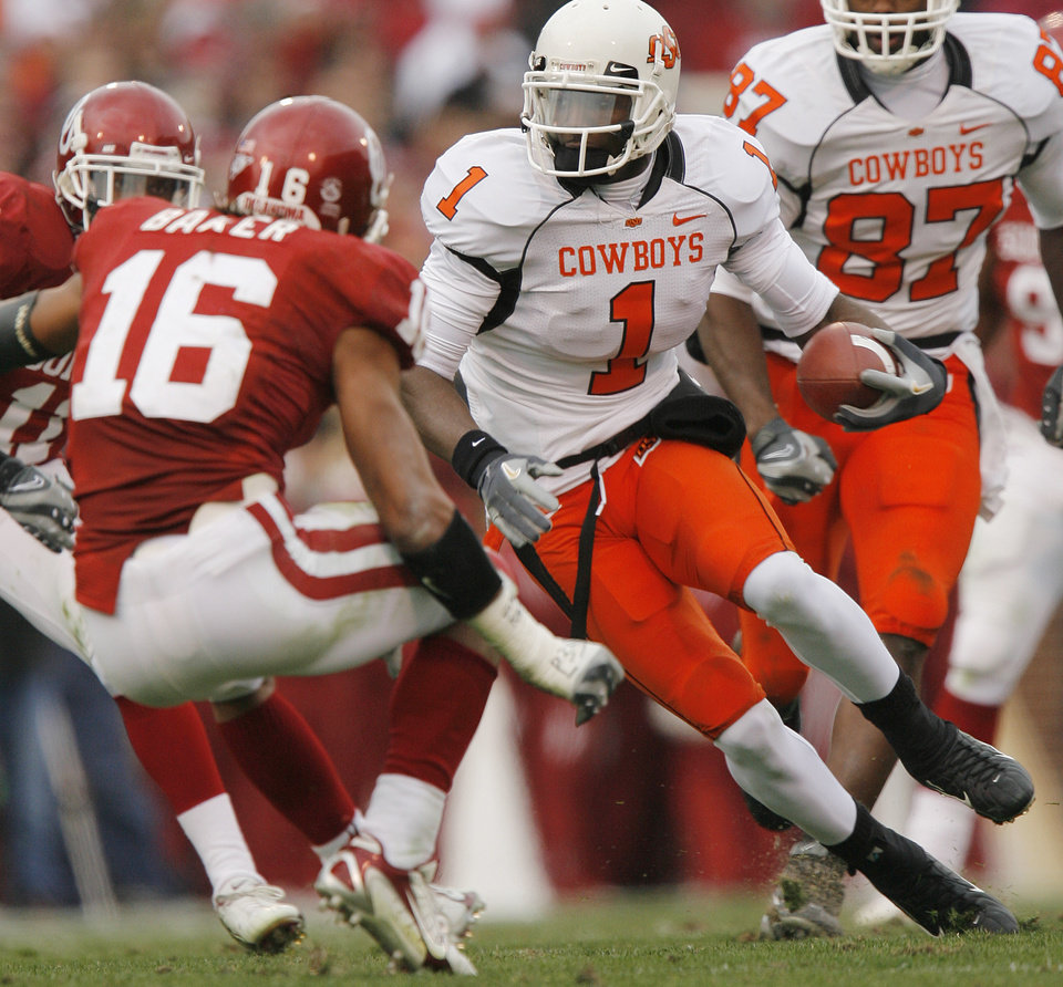 Photo - Oklahoma State's Dez Bryant (1) looks for running room past Oklahoma's Lewis Baker (16) during the first half of the college football game between the University of Oklahoma Sooners (OU) and the Oklahoma State University Cowboys (OSU) at the Gaylord Family-Memorial Stadium on Saturday, Nov. 24, 2007, in Norman, Okla. 