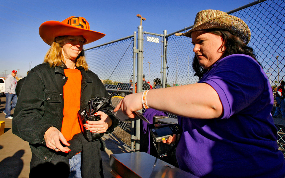Photo - Oklahoma State fan Camille Mardis, of Phoenix, Ariz., walks through the ticket gate before the Insight Bowl college football game between Oklahoma State University (OSU) and the Indiana University Hoosiers (IU) at Sun Devil Stadium on Monday, Dec. 31, 2007, in Tempe, Ariz. 