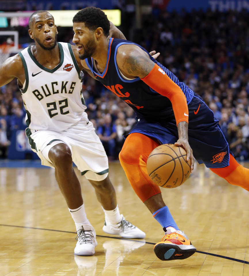 Photo - Oklahoma City's Paul George (13) drives against Milwaukee's Khris Middleton (22) during an NBA basketball game between the Milwaukee Bucks and the Oklahoma City Thunder at Chesapeake Energy Arena in Oklahoma City, Sunday, Jan. 27, 2019. Oklahoma City won 118-112. Photo by Nate Billings, The Oklahoman