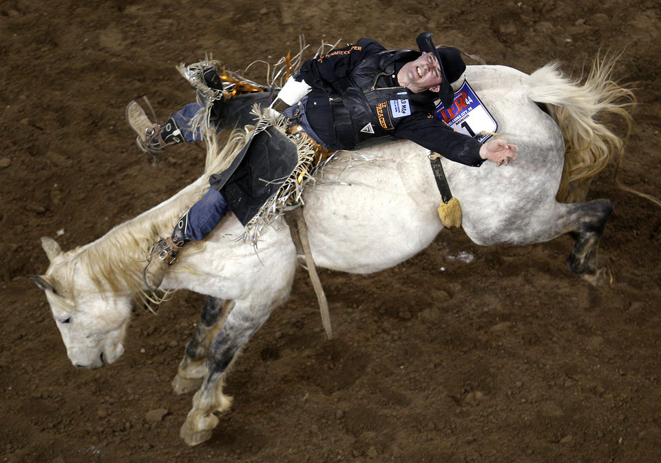 Photo - Shawn Minor of Camden, Ohio, rides in the bareback bronc during the International Finals Rodeo at the State Fair Arena in Oklahoma City, Friday, Jan. 17, 2014.  Photo by Sarah Phipps, The Oklahoman
