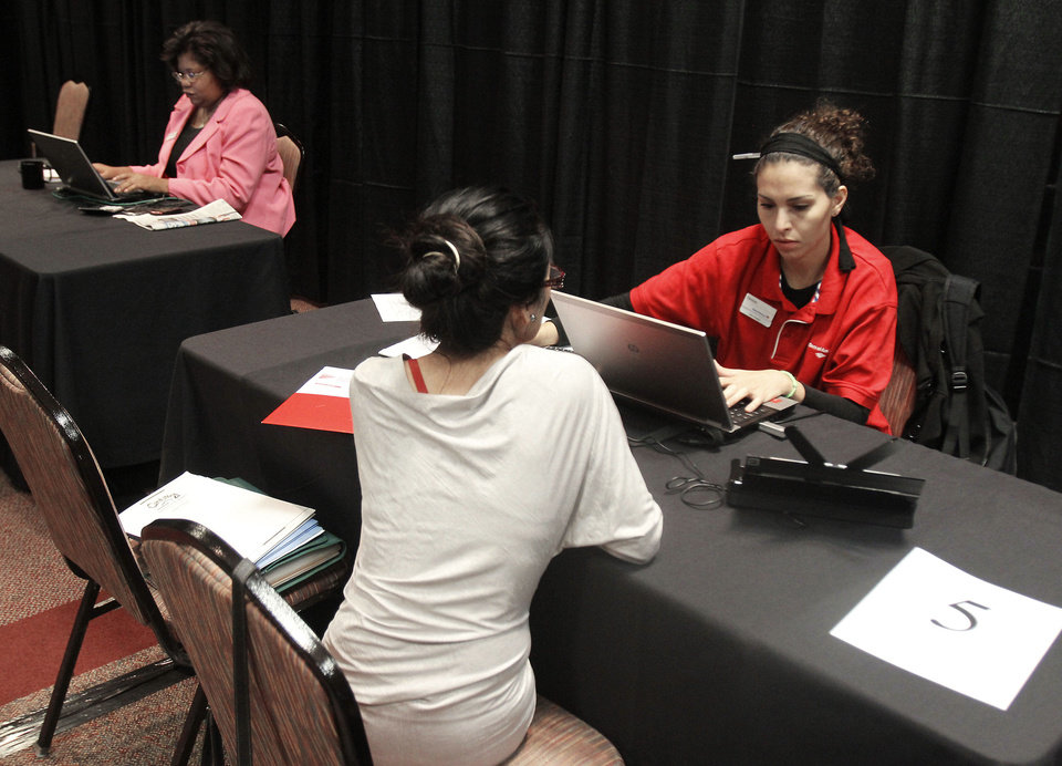 Mortgage specialist Denise Garcia works with a customer as Bank of America holds a homeowners� assistance event Thursday at the Cox Convention Center in Oklahoma City. Customers can come in for guidance about mortgage refinancing, short sales and other options. Photos By Paul Hellstern, The Oklahoman