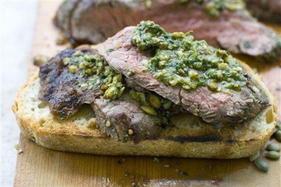 In this June 2011 image taken in Concord, N.H., a chimichurri-like sauce with pepitas tops grilled flank steaks on toasted sourdough bread. (AP Photo/Matthew Mead)