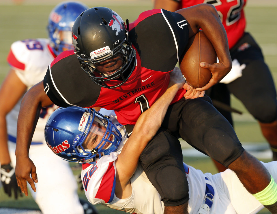 Photo - Lion Blake Brewster (22) tackles Kieron Hardrick (1) as Westmoore plays Moore High School on Friday, Sept. 6, 2013 in Moore, Okla.  Photo by Steve Sisney, The Oklahoman