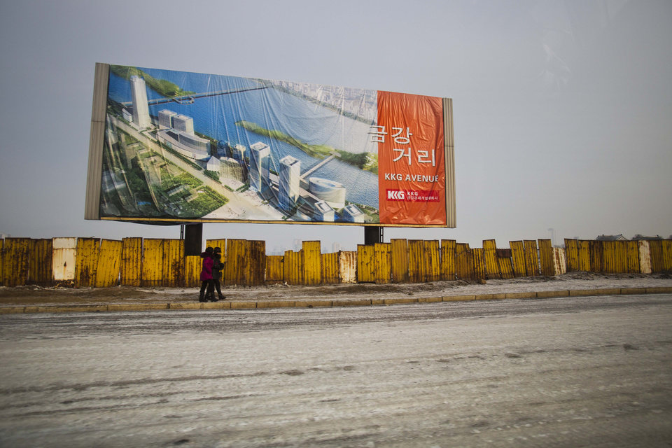 Photo - In this Jan. 11, 2013 photo, a billboard showing a new project under construction stands above the outer fence of the construction site in Pyongyang, North Korea. (AP Photo/David Guttenfelder)