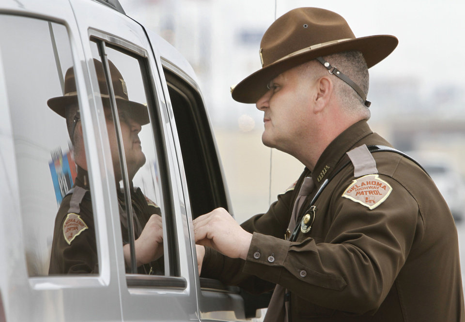 Photo - Oklahoma Highway Patrol trooper Mike Moler talks with a motorist he cited for speeding on Interstate 240 in Oklahoma City on Jan. 25. Photo By Steve Gooch, The Oklahoman  Steve Gooch