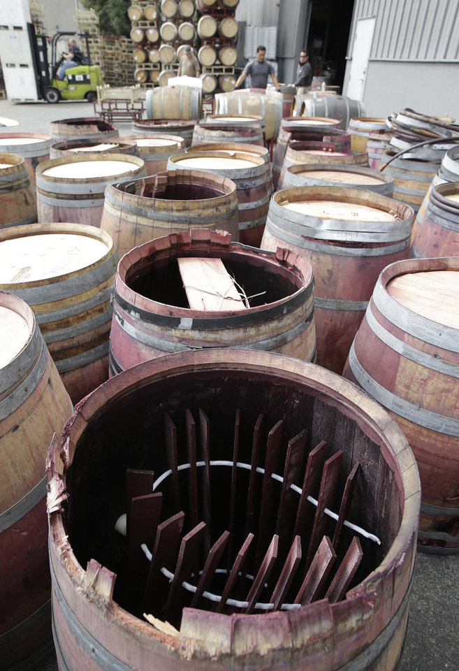 Photo - Earthquake-damaged wine barrels are lined up after being removed from Napa Barrel Care Monday, Aug. 25, 2014, in Napa, Calif. A powerful earthquake that struck the heart of California's wine country caught many people sound asleep, sending dressers, mirrors and pictures crashing down around them and toppling wine bottles in vineyards around the region. The magnitude-6.0 quake struck at 3:20 a.m. PDT Sunday near the city of Napa. (AP Photo/Eric Risberg)